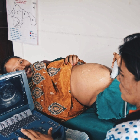 A Nepali woman is all smiles as she receives an ultrasound from a gynaecologist at a CWN health camps